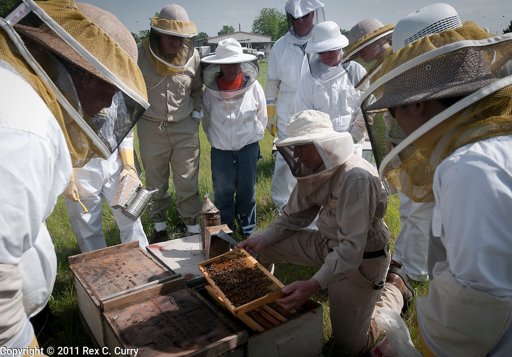 John Talbert shows students in his beekeeping class a frame of honey bees at his Sabine Creek Honey Farm in Royce City on May 7, 2011..