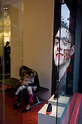 Young girl and mother tries on shoes with male model advertising the Spanish shoe business Camper, in the window of their shop in London's Oxford Street.