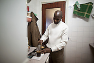 Luis Mendes prepares coffee for guest on January 10 of 2011 at his home in Torrejon de Ardoz, Madrid, Spain. .Luis Mendes is currently an unemployed builder, 45 years old, from Guinea Bissau, and has a wife and 8 children to maintain in Senegal. He lives at his home in Torrejon De Ardoz, Madrid, with his brothers. .Today he is facing a second eviction attempt as he stopped paying the mortgage to Bankia Bank when lost his job in 2009 during the economic crisis. He had to choose between feeding his children or paying the bank. At the moment, he cannot even send money anymore to his family and if he losses his current house, he would gain a live-long debt. He has tried to negotiate with the bank to reach a different solution, by paying a lower monthly fee, but up to now there was no agreement for it..This is also case of many people in Spain that are losing their homes every-days and also gaining debts to banks..According to details of the General Council of the Judiciary, in Madrid there are 40 evictions every-days.
