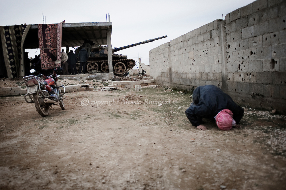 SYRIA - Homs province: A rebels prays nearby a tank whose crew defected from government forces in Homs province on February 22, 2012. ALESSIO ROMENZI