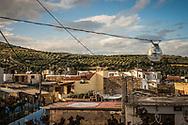 A view over village rooftops towards the hills and olive trees of Crete . Commissioned by PR Media Co.