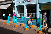 Pedestrians walk past imaginative social distancing markers and barriers using flower pots outside a local restaurant during the Coronavirus pandemic, on 11th July 2020, in Bury St. Edmunds, Suffolk, England.