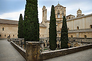 High angle view of the cloister and its tall cypresses, Monestir de Poblet, 1151, Vimbodi, Catalonia, Spain, pictured on May 20, 2006, in the afternoon. Tower of the Cistercian Abbey visible in the background. The Monastery of Poblet belongs to the Cistercian Order and was founded by French monks. Originally, Cistercian architecture, like the rules of the order, was frugal. But continuous additions  including late Gothic and Baroque, eventually made Poblet one of the largest monasteries in Spain which was later used as a fortress and royal palace. It was closed in 1835 by the Spanish State but refounded in 1940 by Italian Cistercians. It is a UNESCO World Heritage Site. Picture by Manuel Cohen.