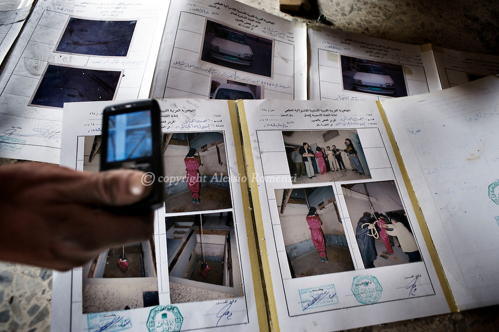 A Libyan man takes a picture with his mobile of pictures showing the hanging of a Chadian man accused of murder in 1992 inside a vandalized police station in Benghazi, Libya on February 25, 2011..ALESSIO ROMENZI