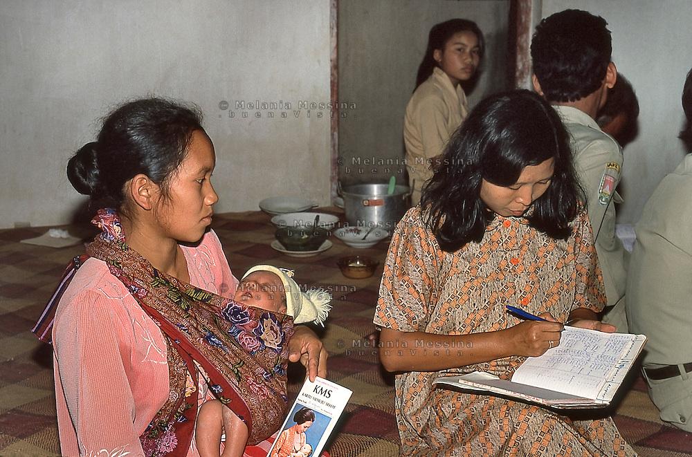 Indonesia; Java, mother and son during the posyandu (training program for the health of children).<br /> Indonesia, Giava, mamma e bambino durante il posyandu (centri sanitari per la salute dei bambini).