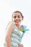 Smiling pre-teen girl holding pinwheel low angle view