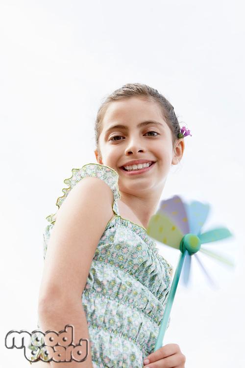 Smiling pre-teen girl holding pinwheel low angle view