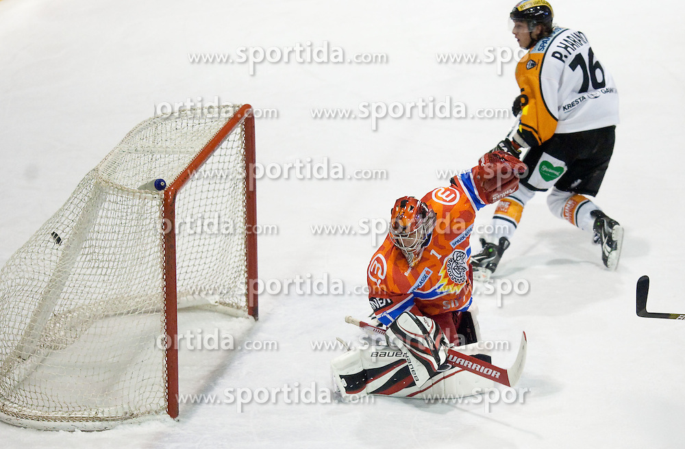 Patrick Harand of Graz scored vs Jaakko Suomalainen of Acroni Jesenice during ice hockey match between HK Acroni Jesenice and  Moser Medical Graz 99ers in 24th Round of EBEL league, on December 3, 2010 in Arena Podmezakla, Jesenice, Slovenia.  (Photo By Vid Ponikvar / Sportida.com)