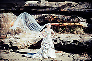 Bride on the beach by rocks with veil flowing in the wind