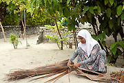 Woman weaving coconut palm thatch.  The island of Utheem. North Maldives.