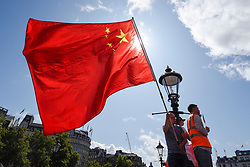© Licensed to London News Pictures. 18/08/2019. LONDON, UK.  A member of the capital's Chinese community waves a Chinese flag during a rally in Trafalgar Square to support the people of Hong Kong and China.  They are calling for an end to police violence and a respect for law as protests in the former British colony enter their eleventh week.  Photo credit: Stephen Chung/LNP