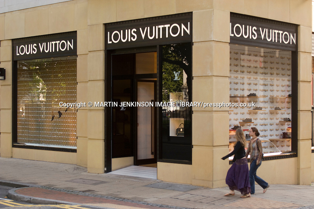 Two women walking past the Louis Vuitton shop in Birmingham ....