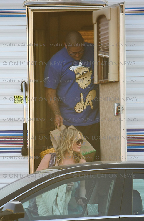 LOS ANGELES, CALIFORNIA - Wednesday 30th JULY 2008 ***EXCLUSIVE*** Hilary Duff Leaves the set of Stay Cool after a day of filming. Hilary's  big tough body guard's duties are to A: keep her safe and B: Carry her bags full of shoes and clothes  to her car for her after filming. Photograph: On Location News. Sales: Eric Ford 1/818-613-3955 info@OnLocationNews.com