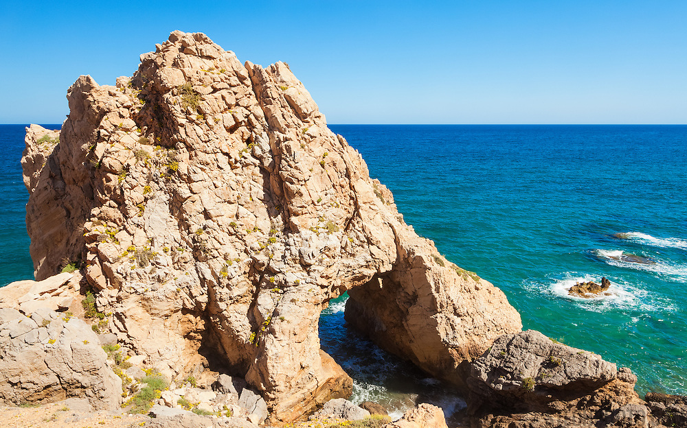 A rock formation and arch on the south eastern coast of Almeria, Spain, in the Cabo de Gata - Níjar Natural Park region.