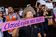 24 MAY 2014 - BANGKOK, THAILAND: A woman holds up a sign against the Thai junta at a shopping mall in Bangkok. There were several marches in different parts of Bangkok to protest the coup that unseated the popularly elected government. Soldiers and police confronted protestors and made several arrests but most of the protests were peaceful. The military junta also announced that firing of several police commanders and dissolution of the Thai Senate. The junta also changed its name from National Peace and Order Maintaining Council (NPOMC) to the National Council for Peace and Order (NCPO).   PHOTO BY JACK KURTZ