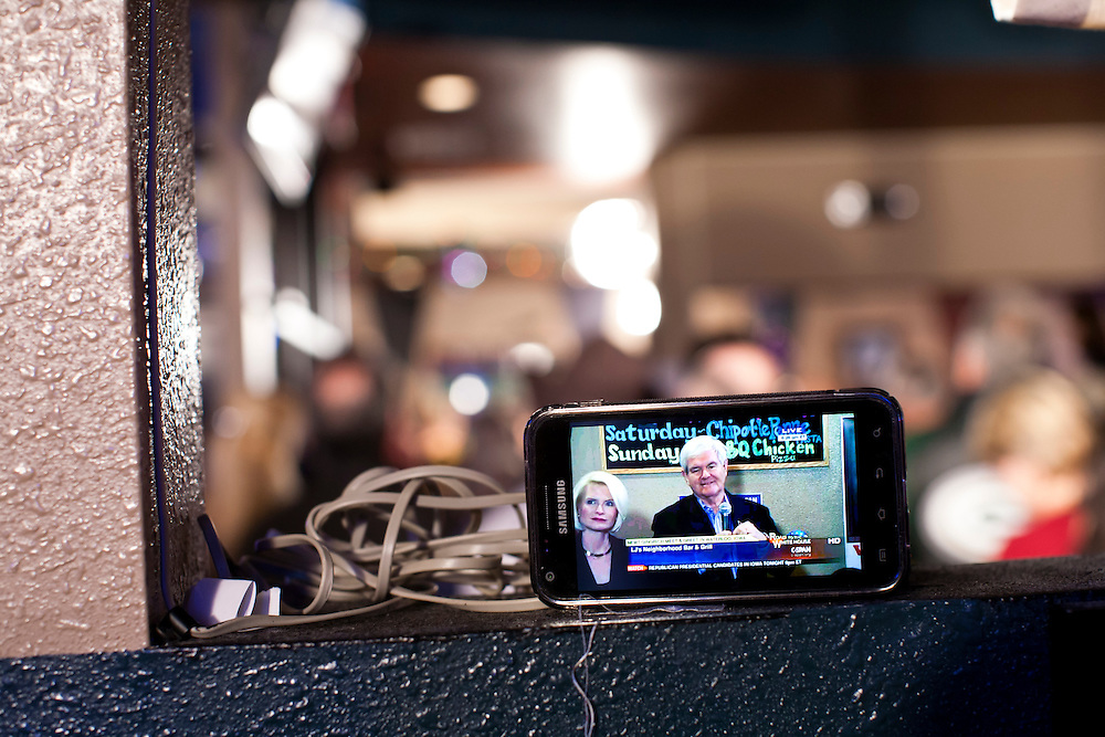 A cell phone streams a live broadcast of C-SPAN's coverage of Republican presidential candidate Newt Gingrich meeting with voters at LJ's Neighborhood Bar & Grill on Sunday, January 1, 2012 in Waterloo, IA.
