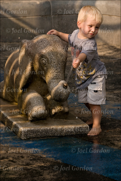 Three year old boy outdoors playing in children's playground with elephant water fountain