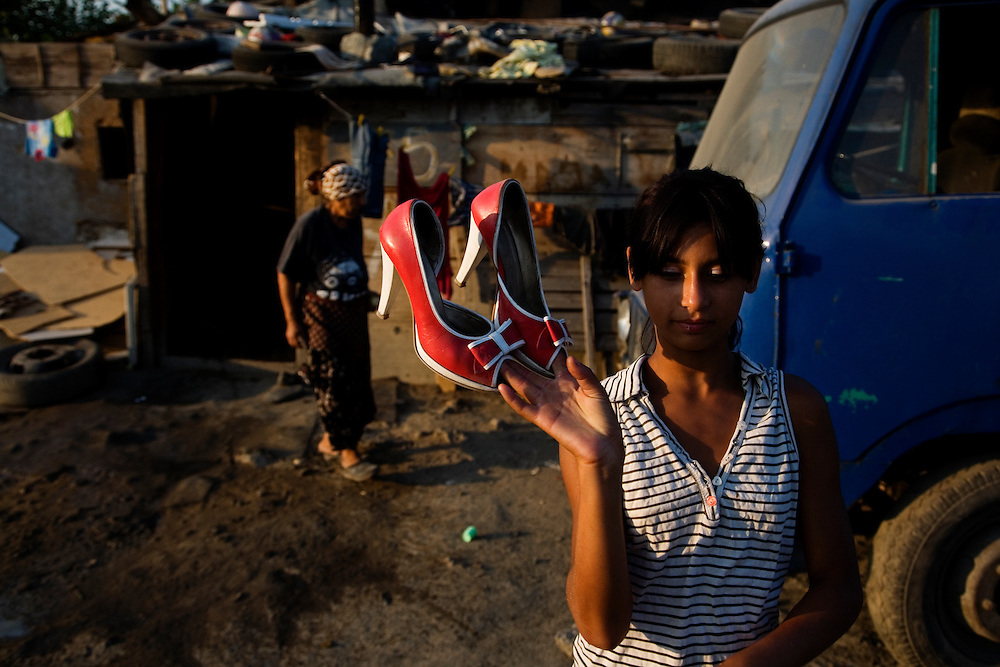 A girl holding a pair of her fanciest shoes in the Nova Gazela settlement.