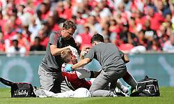Arsenal's Per Mertesacker receives treament before going off injured against Chelsea