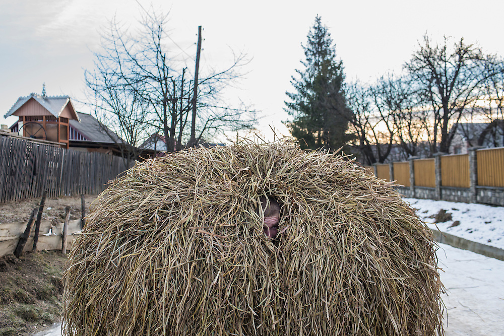KRASNOILSK, UKRAINE - JANUARY 14: A man inside a hay bale costume celebrates the winter festival of Malanka on January 14, 2015 in Krasnoilsk, Ukraine. The holiday, which involves dressing in elaborate costumes and going from house to house as a group singing traditional songs, is celebrated on New Year's Day of the Orthodox calendar, a week after Orthodox Christmas. (Photo by Brendan Hoffman/Getty Images) *** Local Caption ***