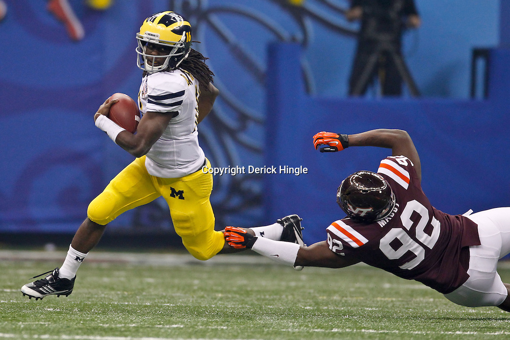 January 3, 2012; New Orleans, LA, USA; Michigan Wolverines quarterback Denard Robinson (16) runs past Virginia Tech Hokies defensive tackle Luther Maddy (92) during the first quarter of the Sugar Bowl at the Mercedes-Benz Superdome.  Mandatory Credit: Derick E. Hingle-US PRESSWIRE