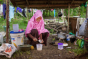 Wahida (27) prepares a bottle of milk for her 2yr old son, Habibi.  She is running low on baby formula. 1500 people were displaced and found shelter in Langaoge coconut farm when a powerful  7.5 earthquake magnitude struck off the coast of Donggala (epicentre) Central Sulawesi, Indonesia on Sept. 28th causing a tsunami and destroying many homes.