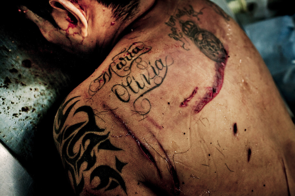 The body of an assasinated young man at the morgue of Instituto Medico Legal in San Salvador, El Salvador. He was shot twice in the face and stabed in several parts of his body. August 15, 2012. Photo/Tomas Munita