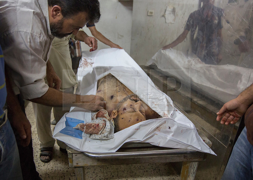 © Licensed to London News Pictures. 17/07/2014. Gaza.   <br /> *WARNING - IMAGE CONTAINS CONTENT OF A GRAPHIC NATURE*<br /> <br /> As the Israel/Gaza conflict enters a 5 hour humanitarian cease fire body of Abed Serhi is prepared for burial after he was killed in an Israeli strike in the Sheikh Ajnein district of Gaza.  Photo credit : Alison Baskerville/LNP