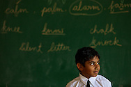 A boy against a blackboard in classroom in Bangalore, India.