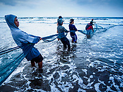 29 JULY 2017 - AIRKUNING, BALI, INDONESIA: Fishermen in Airkuning, a Muslim fishing village on the southwest corner of Bali, haul in a fishing net that had been laid by outrigger canoes from the village. Villagers said their regular catch of fish has been diminishing for several years, and that are some mornings that they come back to shore with having caught any fish.    PHOTO BY JACK KURTZ
