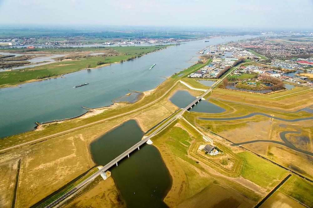 Nederland, Noord-Brabant, Werkendam, 01-04-2016; <br /> Ruimte voor de Rivier project Ontpoldering Noordwaard. <br /> Foto richting Werkendam, rivier de Nieuwe Merwede links.  De bandijk (winterdijk) is  voorzien van doorlaten annex brug, boerderijen zijn op terpen gebouwd. De dijken aan de rivierzijde zijn gedeeltelijk afgegraven waardoor rivier de Nieuwe Merwede bij hoogwater via de Noordwaard sneller naar zee stromen. Gevolg van de ingrepen is dat de waterstand verder stroomopwaarts zal dalen. Ook de getijden keren terug in het gebied.<br /> National Project Ruimte voor de Rivier (Room for the River) By lowering and moving the dike of the Noordwaard polder the area will become subject to controlled inundation and function as a dedicated water detention district. Houses and farmhouses will be constructed on new dwelling mounds.<br /> <br /> luchtfoto (toeslag op standard tarieven);<br /> aerial photo (additional fee required);<br /> copyright foto/photo Siebe Swart