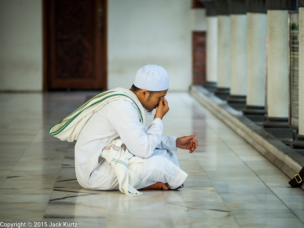 06 JUNE 2015 - KUALA LUMPUR, MALAYSIA: A man prays in the Masjid Jamek in Kuala Lumpur. Built in 1909, Jamek Mosque is one of the oldest mosques in Kuala Lumpur. It is located at the confluence of the Klang and Gombak River and was designed by Arthur Benison Hubback. The mosque was a built in the style of Mughal (northern India) architecture. Before the national mosque, Masjid Negara, was opened in 1965, Masjid Jamek served as Kuala Lumpur's main mosque.      PHOTO BY JACK KURTZ