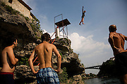 "Øyvind, a 20year old Norwegian tourist, practices his technique from the 10m platform under the watchful eye of veteran Mostari Adem Mocca Pajevic before attempting his jump from the Old Bridge...Divers and tourists at Mostar's famous Old Bridge (Stari Most) in Bosnia and Herzegovina. This bridge is the city and region's biggest tourist attraction and there are busses full of tourists coming in from Sarajevo and Dubrovnik, Croatia. For 25euros tourists can train to jump from the bridge themselves, under supervision from the ""professional"" Mostar divers known as the Mostari. .."