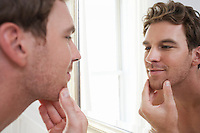 Unshaven Man Looking in Bathroom Mirror