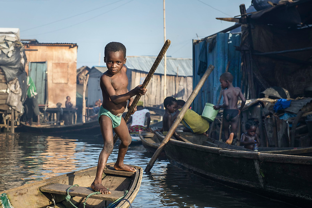 A young boy, storing his takings in his underwear, paddles his canoe-taxi along one of the many Makoko channels.