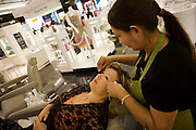 "Lying horizontal in a busy salon, a lady passenger receives eyebrow threading treatment during a beauty session at the Blink Eyebrow Bar in World Duty Free, Heathrow Airport's terminal 5. The beautician holds the thread that squeezes the woman's eyebrow follicles, removing the tiniest and finest hair right from the root. Threading is a technique that China has been using for centuries but has recently become popular in western countries. Amid the busy departures terminal of this international aviation hub, this is a corner of quiet and tranquillity before the woman traveller boards her business flight after this few minutes of pampering. From writer Alain de Botton's book project ""A Week at the Airport: A Heathrow Diary"" (2009)."