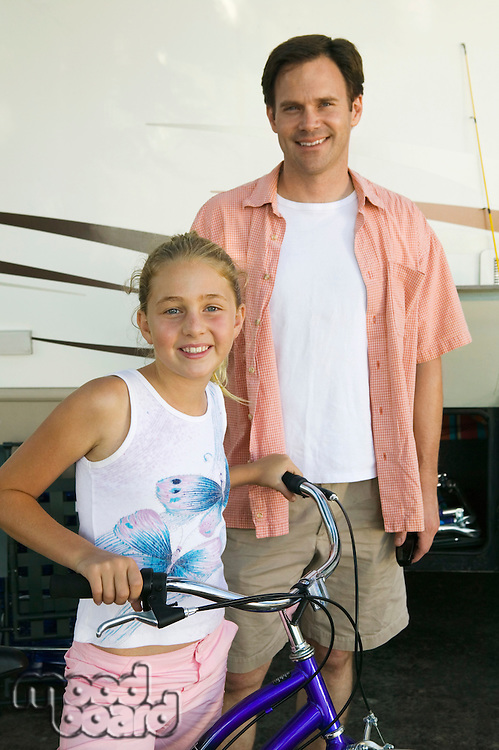 Father with Daughter on Bike Next to RV
