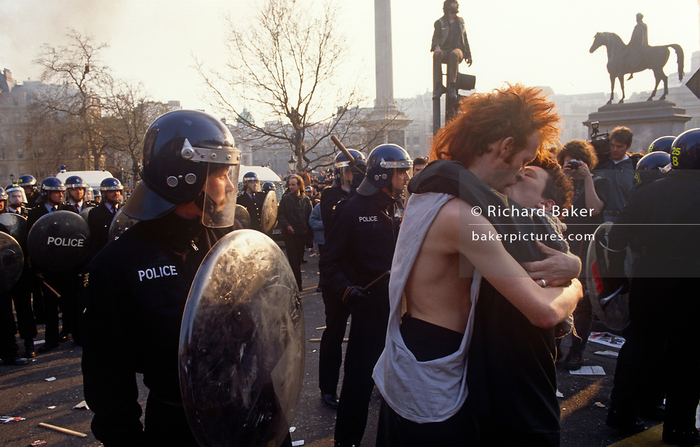 A couple kiss near police officers in the middle of the Poll Tax riot in the UK capital, on 31st March 1990, in Trafalgar Square, London, England. Angry crowds, demonstrating against Margaret Thatcher's local authority tax, stormed the Whitehall area and then London's West End, setting fire to a construction site and cars, looting stores up Charing Cross Road and St Martin's Lane. The anti-poll tax rally in central London erupted into the worst riots seen in the city for a century. Forty-five police officers were among the 113 people injured as well as 20 police horses. 340 people were arrested.