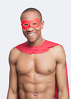 Portrait of young shirtless man in superhero costume smiling against gray background