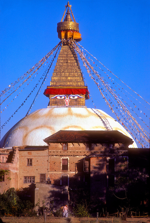 The eyes of the compassionate Lord Buddha watch over the Kathmandu Valley from this great stupa -- a kind of Buddhist shrine -- adorned with prayer flags and a tapering golden tower, while in the forground a woman carrying a basket on her back strides into a field.