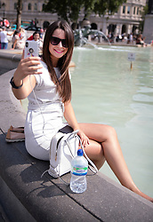 © Licensed to London News Pictures. 26/07/2018. London, UK. A tourist takes a selfie as she cools off in the Trafalgar Square fountains as London experiences the hottest day of the year so far. Photo credit: Peter Macdiarmid/LNP