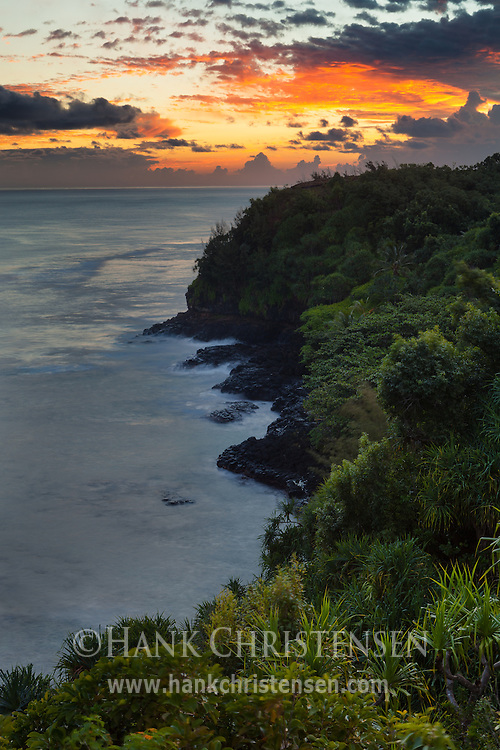 Clouds to the east light up over Kauai's north shore at sunrise