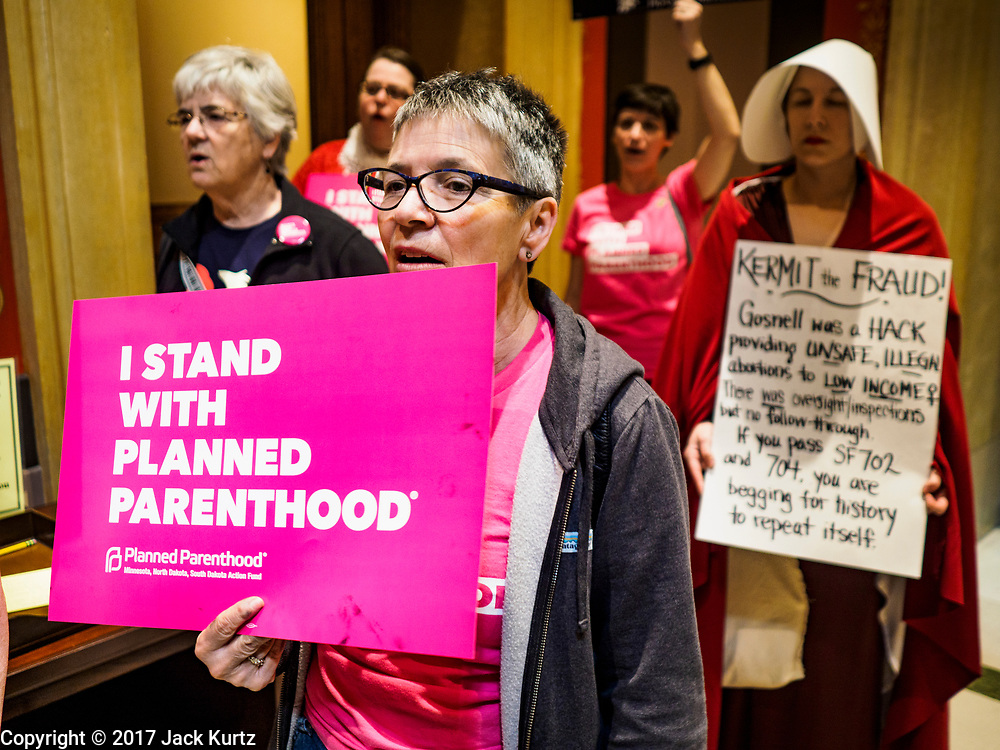 "04 MAY 2017 - ST. PAUL, MN: Women, including one dressed as a handmaid (from the novel and Hulu series ""A Handmaid's Tale""), chant for choice and access to reproductive health care during a rally to protect women's access to health care at the Minnesota Capitol. About 50 people came to a protest to urge Minnesota State Senators to vote against two bills supported by the Republican party that would restrict access to women's health care in Minnesota. The protest was organized by  NARAL Pro-Choice Minnesota, NCJW Minnesota, and Planned Parenthood Minnesota. The Senate passed the bills but Minnesota's Democratic governor is expected to veto the legislation when it reaches his desk.     PHOTO BY JACK KURTZ"