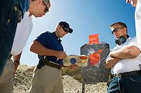 Men watching instructor at combat training in desert