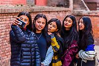 A group of teenage Nepalese girls taking a selfie in Durbar Square, Bhaktapur, Kathmandu Valley, Nepal.
