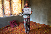 """Insha Majid, 12, holds a sign with the message """"I was afraid when water came in my house"""" in her house, in Purnishadashah village, Jammu and Kashmir, India, on 24th March 2015. The floods happened at night when the banks of the Jhelum river broke, forcing flood-affected families to scramble for higher ground. Photo by Suzanne Lee for Save the Children"""