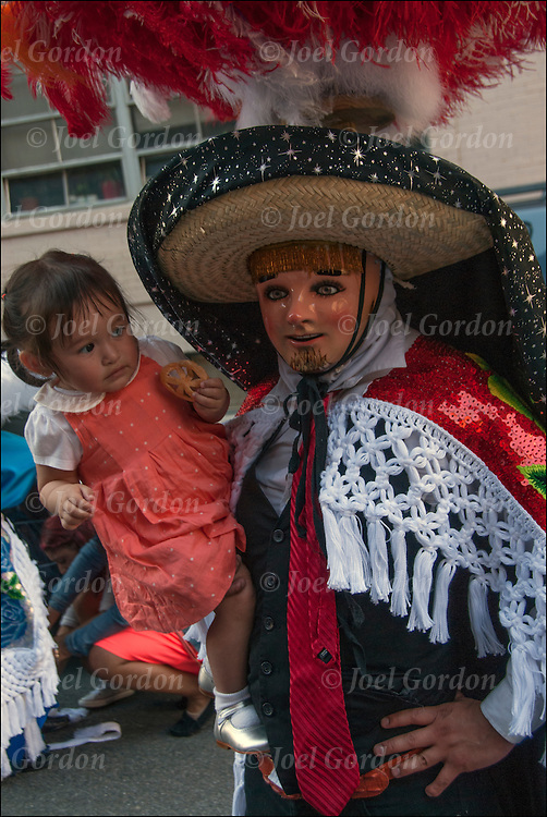 Mexican Pride on Mothers Day at block party in West Village off 9th Avenue in New York City,<br /> <br /> Mexican American dressed in traditional Huehitzungo Carnival costume and mask holding toddler daughter, shows his ethnic pride for Mexico.