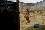 Australian volunteer Cassie throws her hair as for drying it as she leaves a makeshift shower at a campsite in the outskirts of  Lima, Peru, Friday, November, 2015.