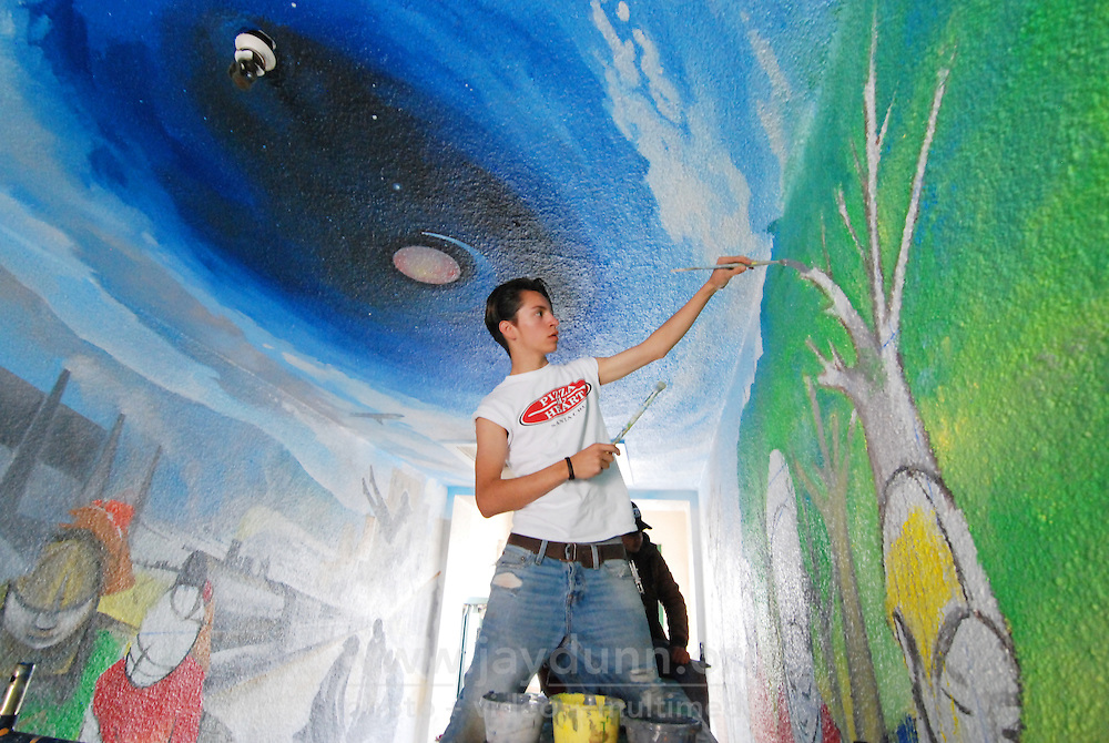 Josué David Rubio, 18, of Hijos del Sol, working on a new mural commemorating Roosevelt School's 90th anniversary last year.
