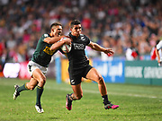 New Zealand All Blacks player Bailey Simonsson is tackled from behind in the game New Zealand All Blacks vs South Africa during the Cathay Pacific/HSBC Hong Kong Sevens festival at the Hong Kong Stadium, So Kon Po, Hong Kong. on 8/04/2018. Picture by Ian  Muir.